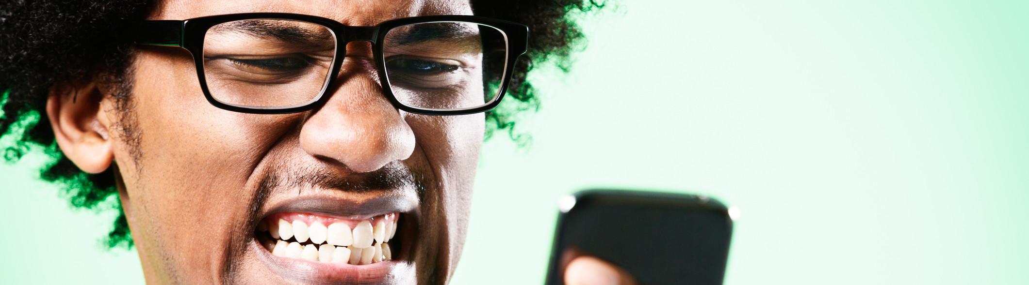 Man wincing at phone