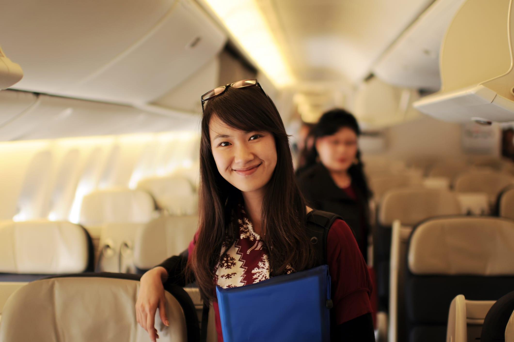 Woman Walking Down an Airplane Aisle