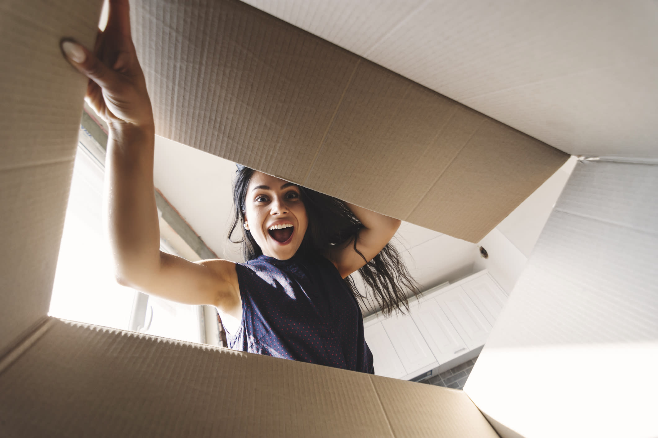 Smiling woman opening a cardboard box