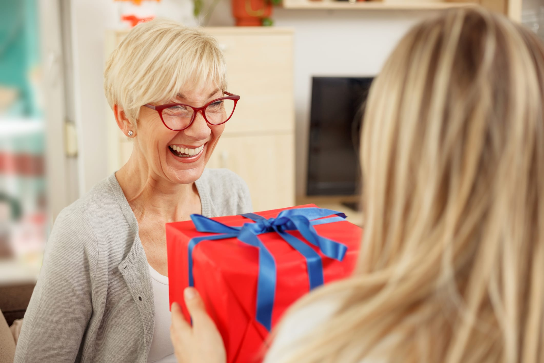 woman gives gift to mother