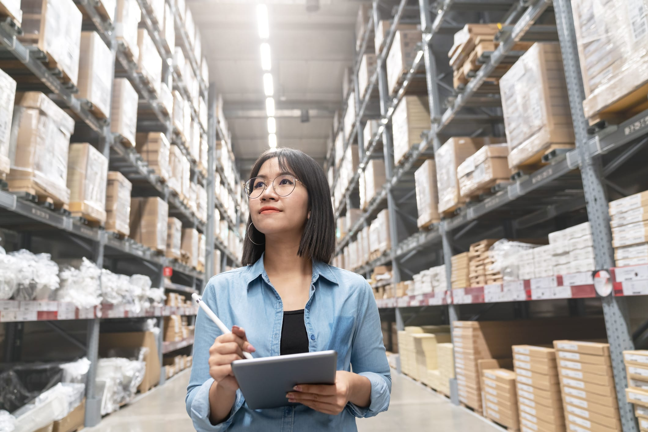An Asian Woman Reviewing Inventory in Warehouse