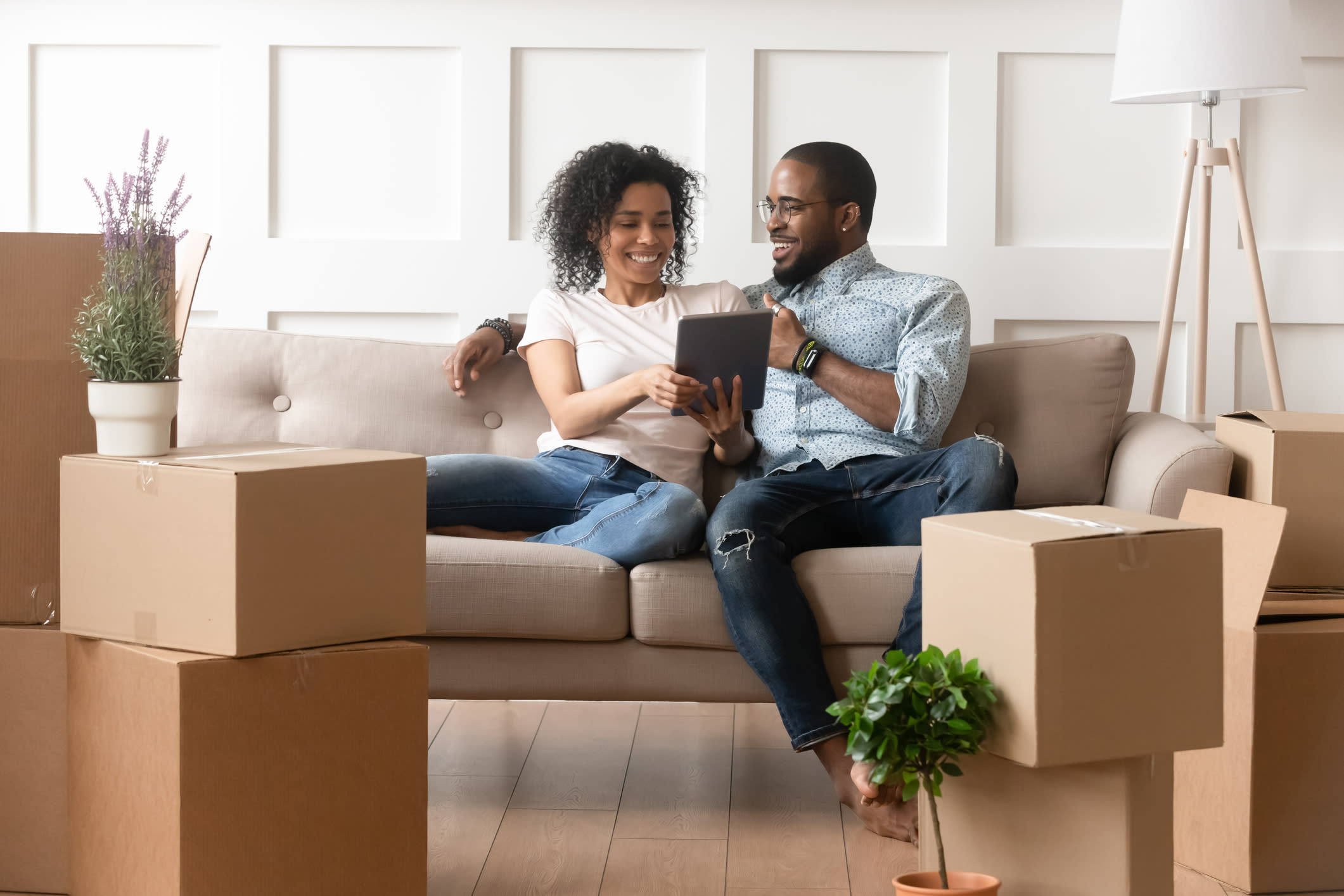 Couple Sits on a Couch Looking at a Tablet