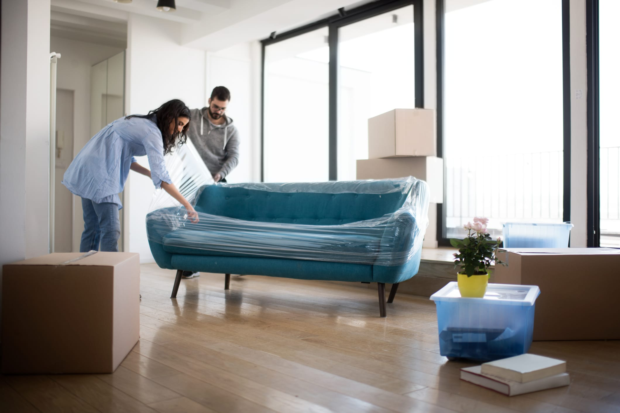 Young Couple Unwrapping a Sofa in Their Apartment