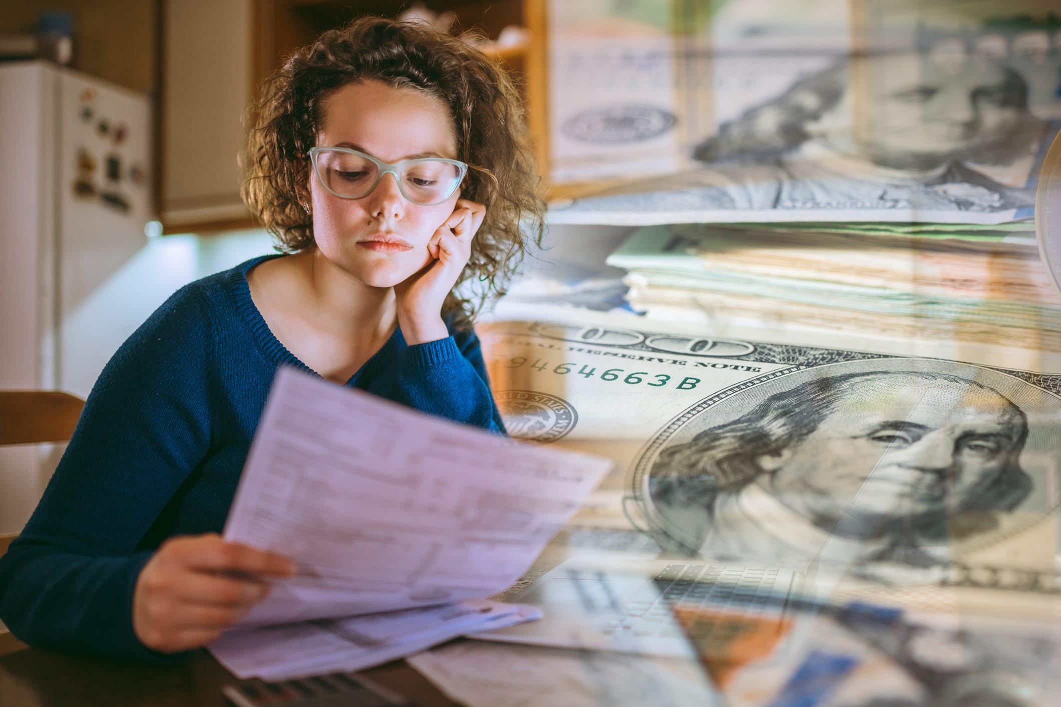 woman paying bills thinking of cash