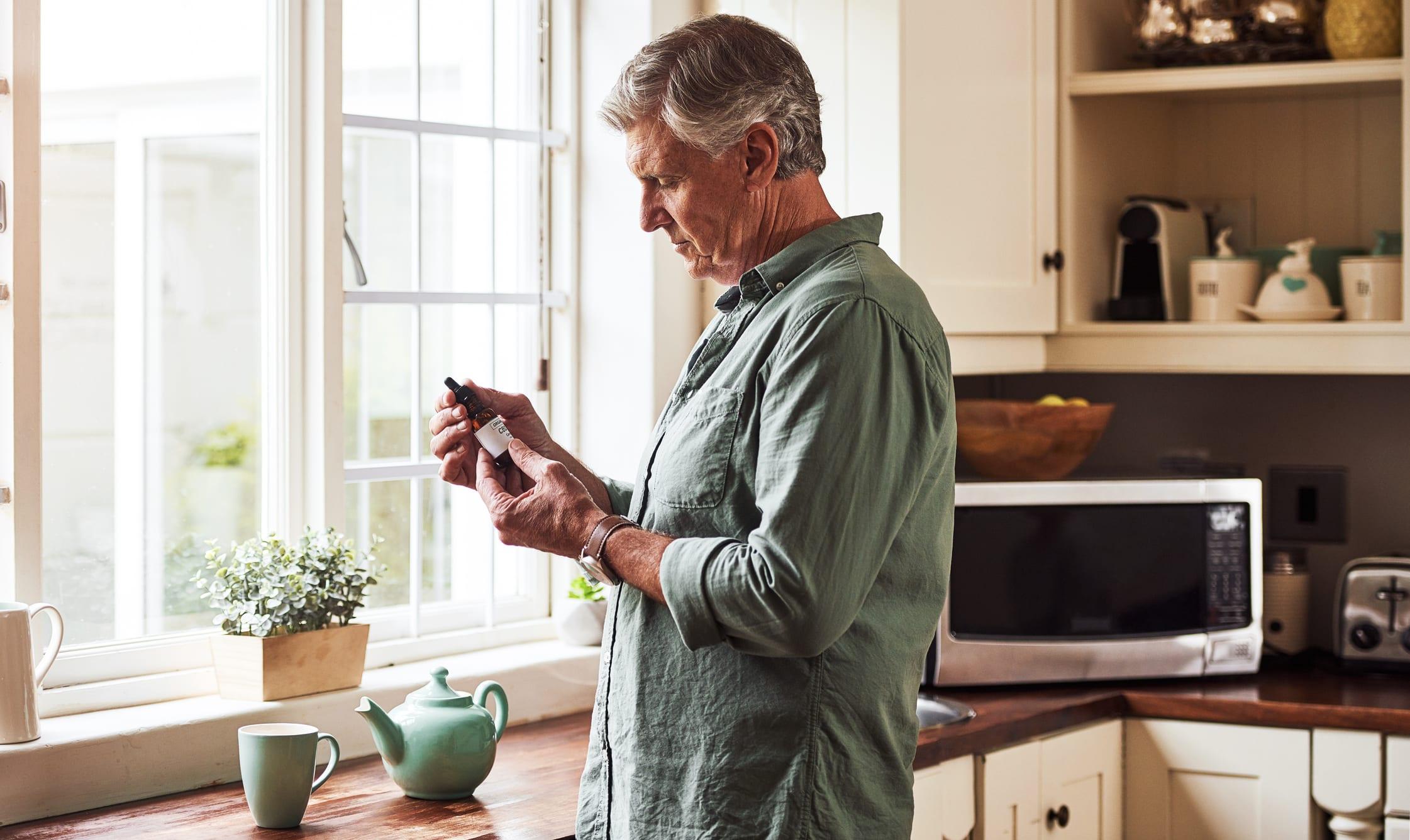 Man Preparing a Cup of Tea with CBD Oil