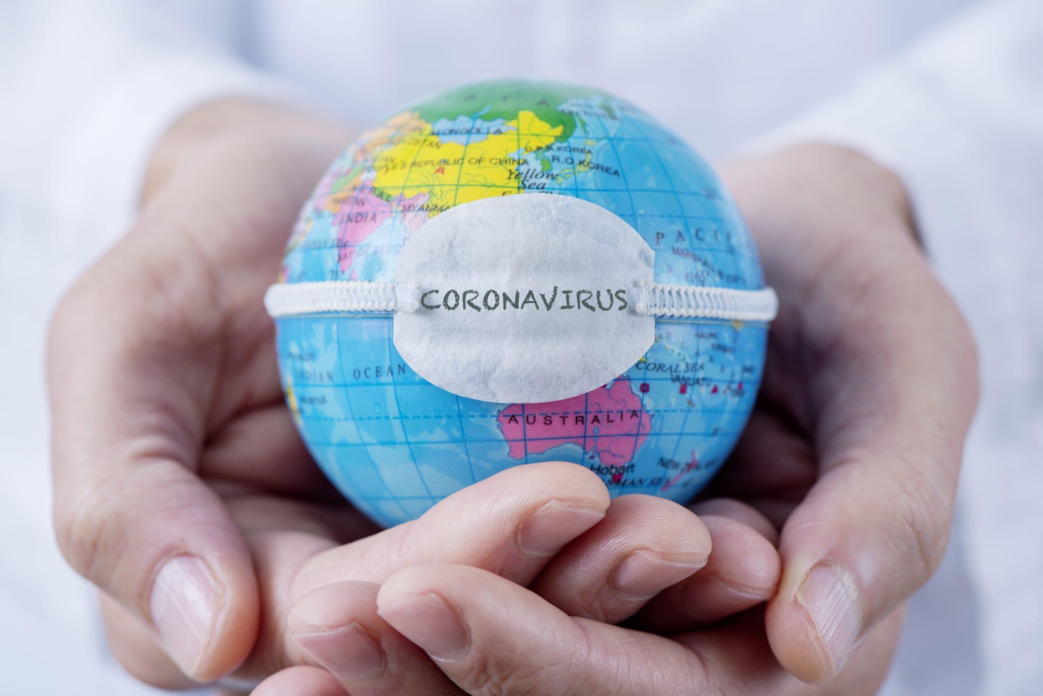 person holding coronavirus globe