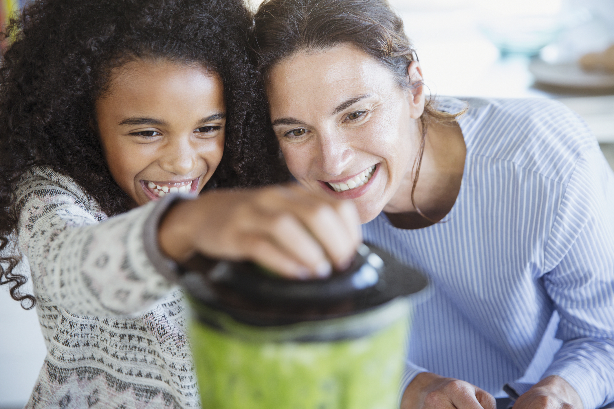 mom and daughter make smoothie